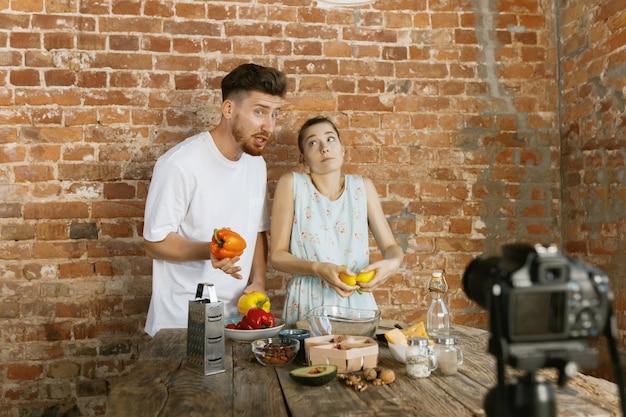 Junges paar kocht und nimmt live-video für vlog und soziale medien auf