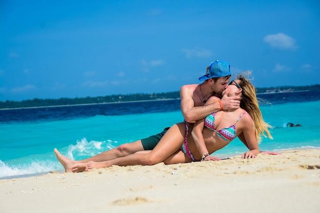 Junges paar küssen sich im urlaub am strand liegend