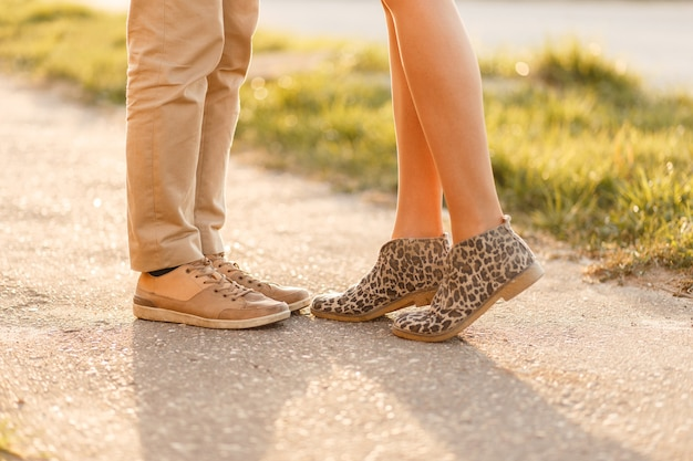 Junges paar küsst bei sonnenuntergang. beine mit stylischen schuhen