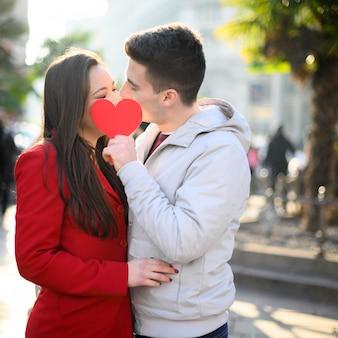 Junges paar küsst und bedeckt sich mit einem herzförmigen karton