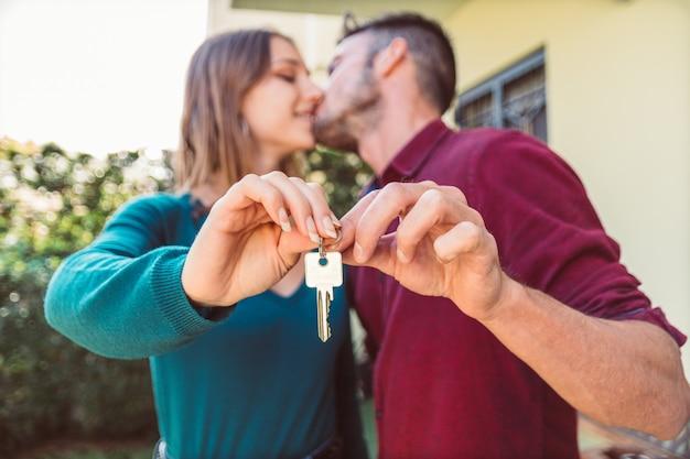 Junges paar küsst und hält neuen hausschlüssel hoch.