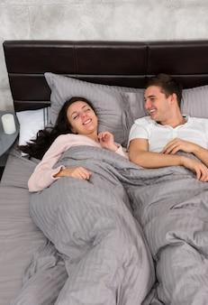 Junges paar lacht und trägt pyjamas, während es im bett im schlafzimmer im loft-stil mit grauen farben liegt