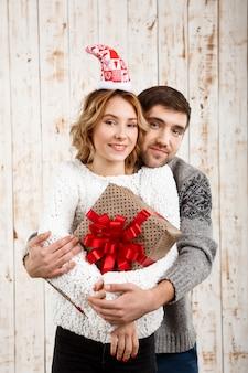 Junges paar lächelnd umarmend, das weihnachtsgeschenk über hölzerner oberfläche hält
