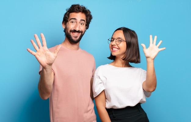 Junges paar lächelt und sieht freundlich aus, zeigt nummer fünf oder fünften mit der hand nach vorne und zählt herunter