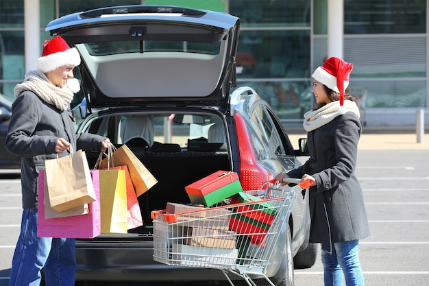 Junges paar lädt weihnachtseinkäufe in den kofferraum des einkaufszentrums