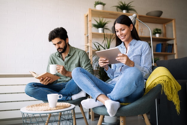 Junges paar liest zusammen buch und e-book, sitzt auf der couch
