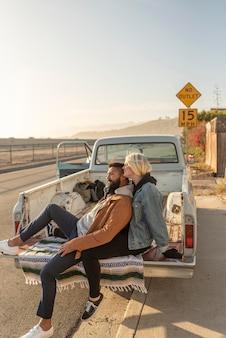 Junges paar macht eine pause auf der rückseite ihres autos