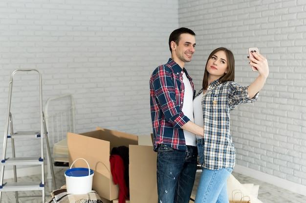 Junges paar macht selfie beim umzug in eine neue wohnung