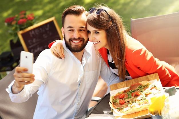 Junges paar macht selfie in einem restaurant
