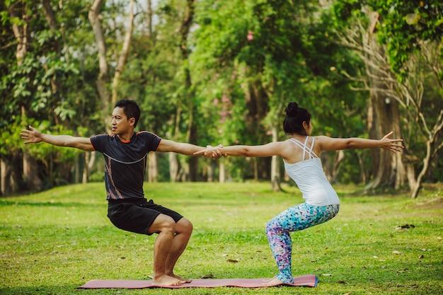 Junges paar macht yoga zusammen in der natur