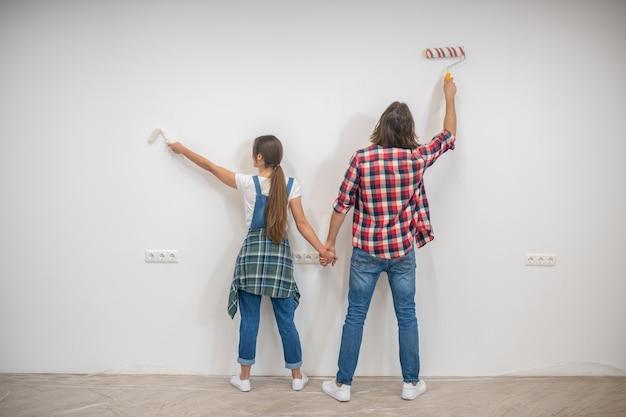 Junges paar malt wände und händchen haltend