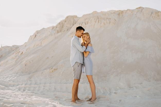 Junges paar mann und frau, die draußen in der wüste umarmen.