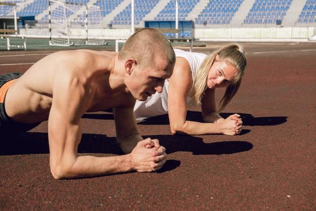 Junges paar, mann und frau, die plankenübungen bei den bauchmuskeln im stadion und beim kortextraining machen?