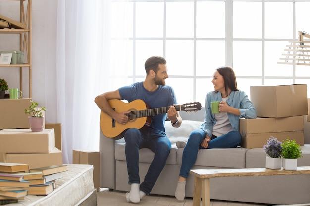 Junges paar, mann und frau, die zusammen in eine neue wohnung ziehen und gitarre spielen?