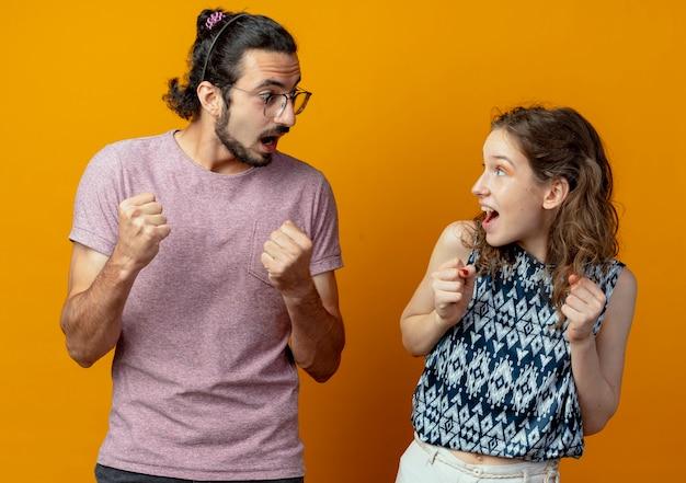 Junges paar mann und frau glücklich und aufgeregt geballte fäuste freuen sich über ihren erfolg über orange wand