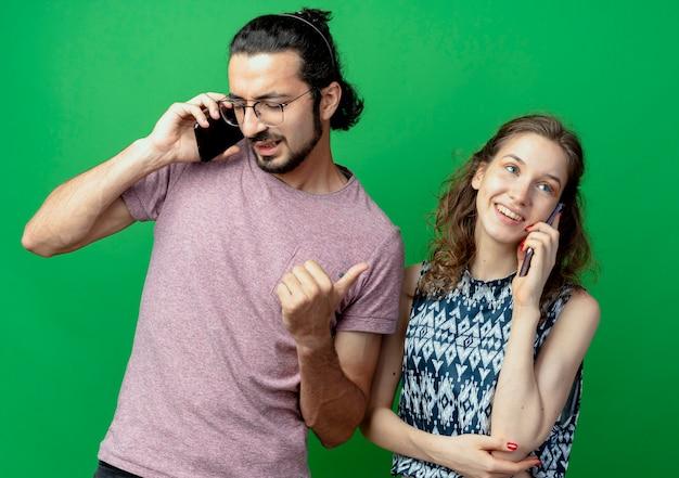 Junges paar mann und frau, glücklich und positiv sprechen auf handys, die über grüner wand stehen