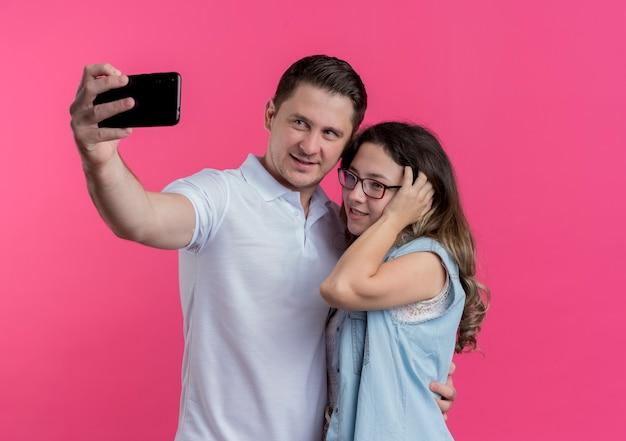 Junges paar mann und frau in freizeitkleidung unter selfie lächelnd glücklich in der liebe stehen zusammen über rosa wand