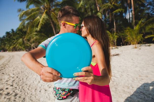 Junges paar mann und frau spielen fliegende scheibe am tropischen strand, sommerferien, liebe, romantik, fröhliche stimmung, lächeln, spaß haben, hipster-outfit, sonnenbrille, jeansshorts, sonnig, positive stimmung