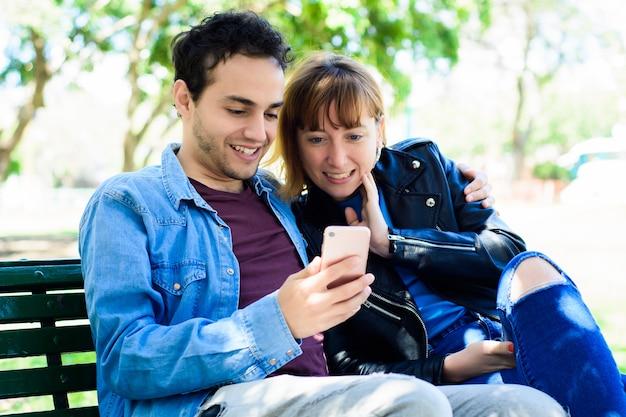 Junges paar mit anwendung auf dem smartphone