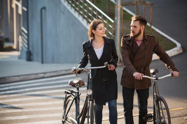 Junges paar mit auf einem fahrrad gegenüber stadt
