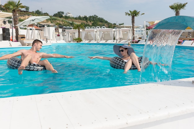 Junges paar mit aufblasbarem rettungsring, der versucht, seine hände beim genießen im pool in einem resort zu erreichen.
