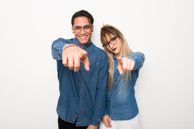 Junges paar mit brille zeigt finger auf sie mit einem überzeugten ausdruck