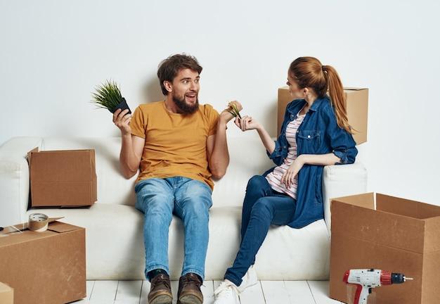 Junges paar mit dingen in kisten auf der couch, die einweihungsfeier bewegt