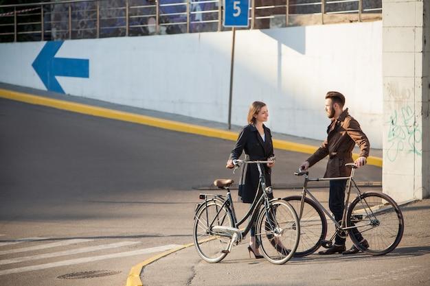 Junges paar mit einem fahrrad gegenüber stadt
