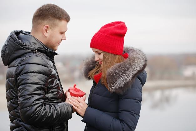 Junges paar mit einem geschenk in ihren händen. das konzept für den valentinstag