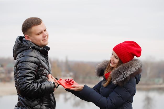 Junges paar mit einem geschenk in ihren händen