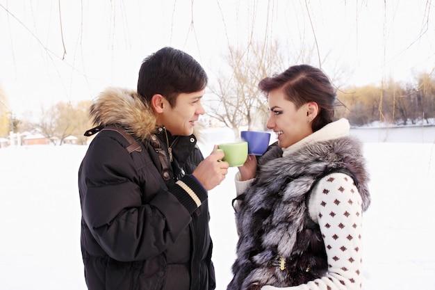 Junges paar mit einem heißen getränk im winter draußen