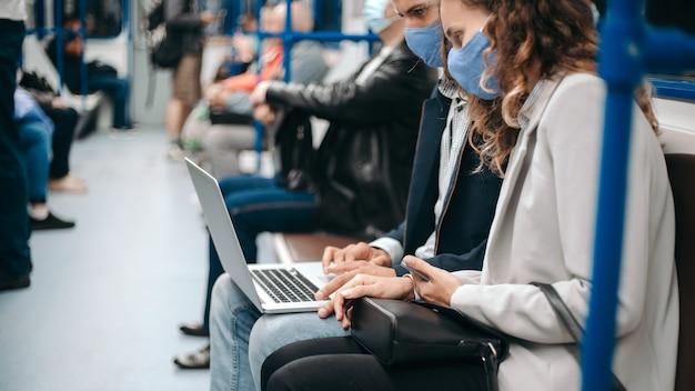 Junges paar mit einem laptop, der in einem u-bahnwagen sitzt