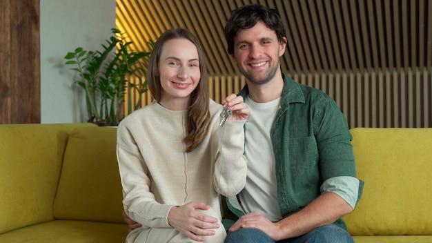 Junges paar mit einem schlüssel zu ihrem neuen zuhause, das auf einem gelben sofa sitzt