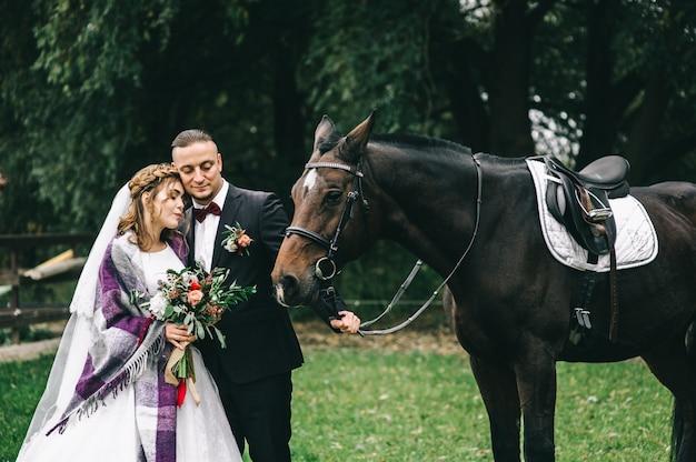Junges paar mit einem schwarzen pferd im park