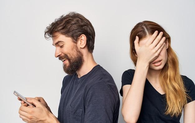 Junges paar mit einem telefon in den händen emotionen familienkommunikation unzufriedenheit