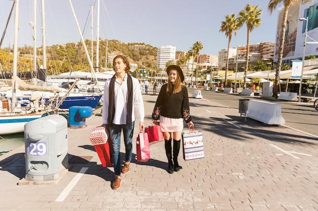 Junges paar mit einkaufstüten gehen