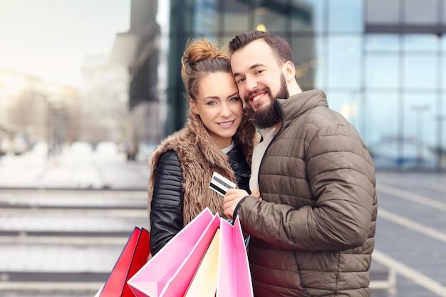 Junges paar mit einkaufstüten und kreditkarte in der stadt