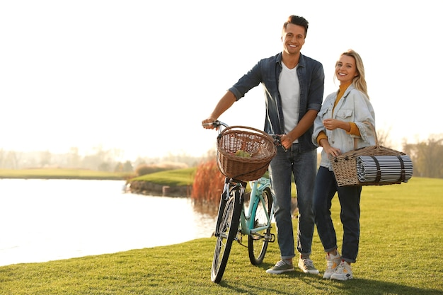 Junges paar mit fahrrad und picknickkorb in der nähe des sees an einem sonnigen tag