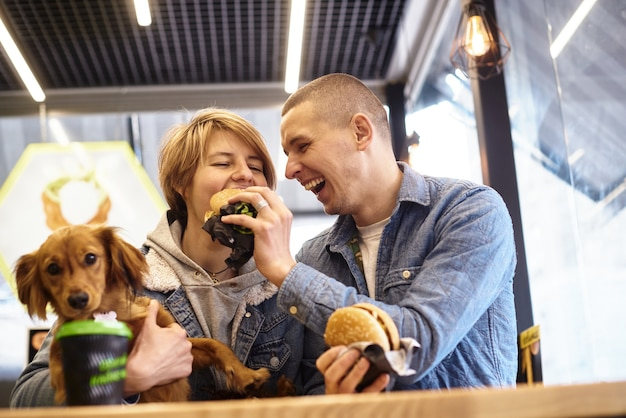 Junges paar mit hund beim fast-food-mittagessen