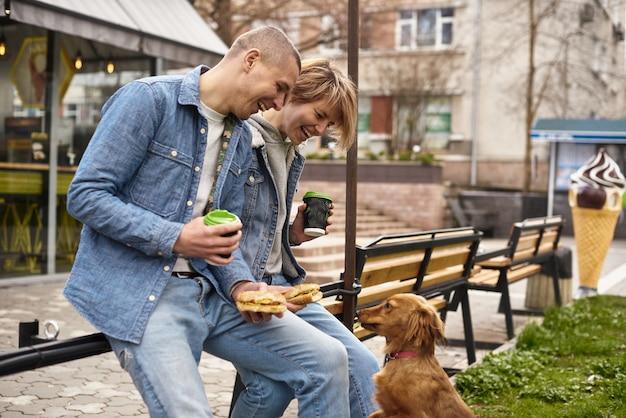 Junges paar mit hund, der fast-food-mittagessen hat