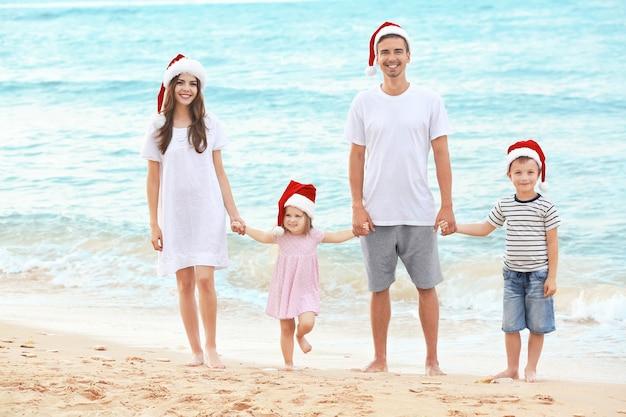 Junges paar mit kindern am strand. weihnachtskonzept