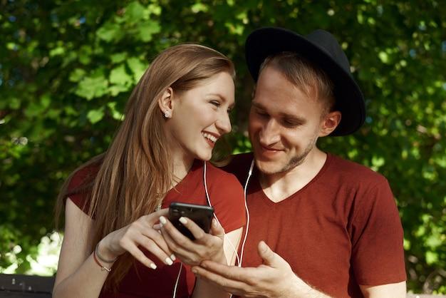 Junges paar mit kopfhörern und einem telefon in einem park