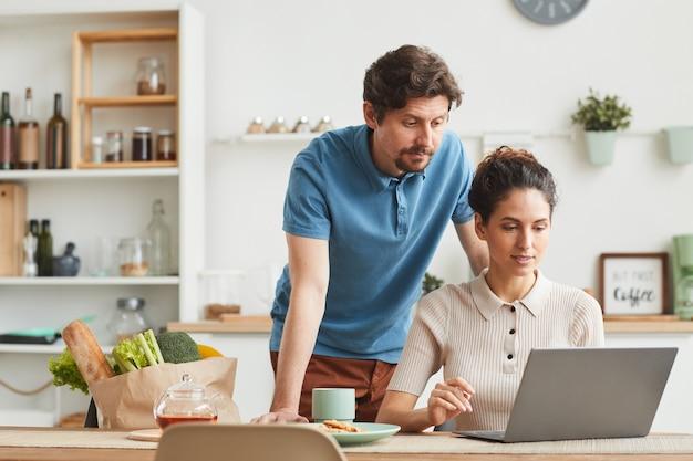 Junges paar mit laptop-computer zu hause bestellen sie produkte online
