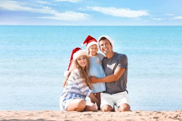 Junges paar mit nettem mädchen am strand. weihnachtsfeier konzept
