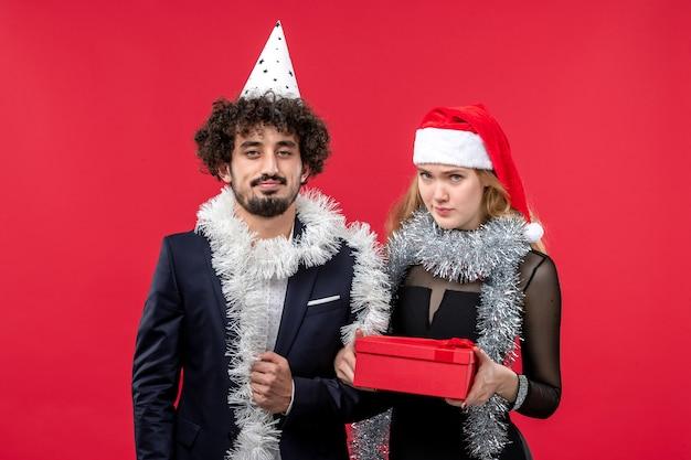 Junges paar mit neujahrsgeschenk partyfarbe weihnachtsliebe