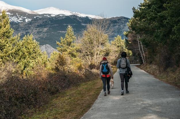 Junges paar mit rucksäcken und einem hund auf der straße mit schneebedeckten bergen im hintergrund