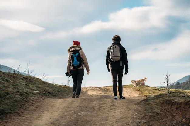Junges paar mit rucksäcken und einem hund, der in den bergen spazieren geht, mann und frau warm gekleidet auf wanderer