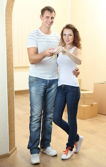 Junges paar mit schlüssel zu ihrem neuen zuhause im zimmer