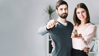 Junges Paar mit Schlüsseln und Haus
