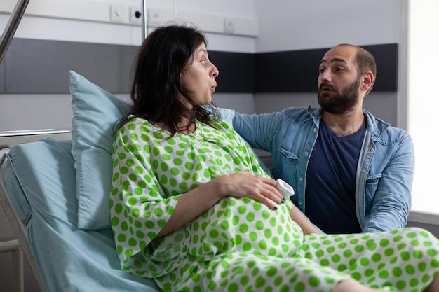 Junges paar mit schwangerschaft sitzt im krankenbett